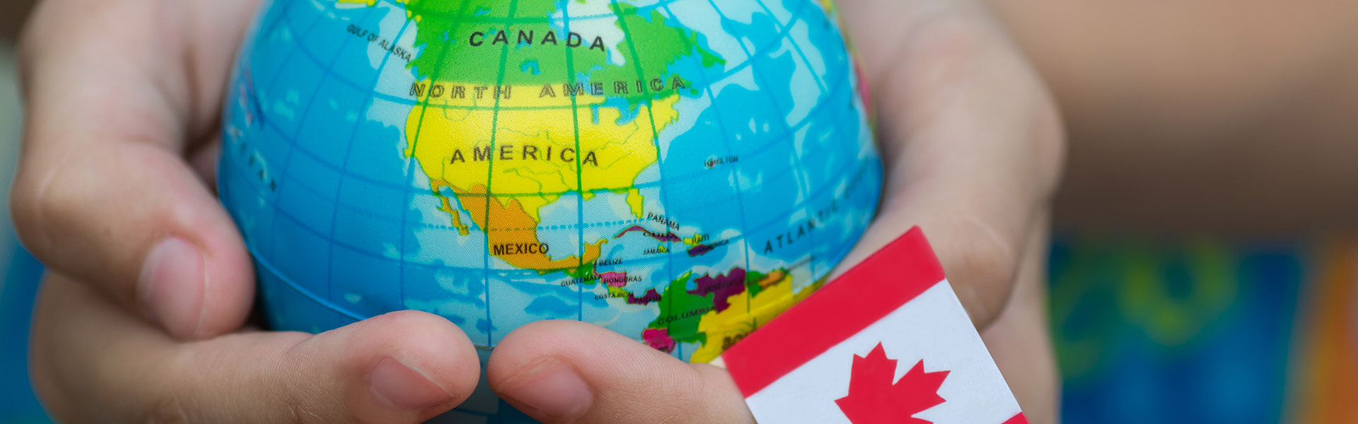 A globe showing North America being held in hands with a Canadian flag coming up from the right bottom corner of the image.