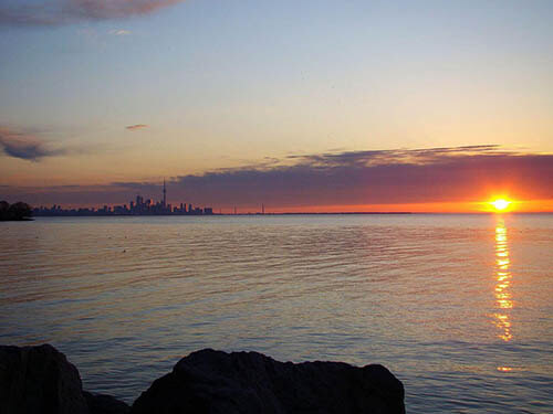 A sunset skyline of Toronto, ON, showing the CN tower and downtown.