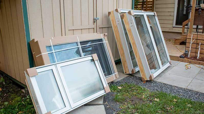 A set of Nordik Windows leaning on a shed.