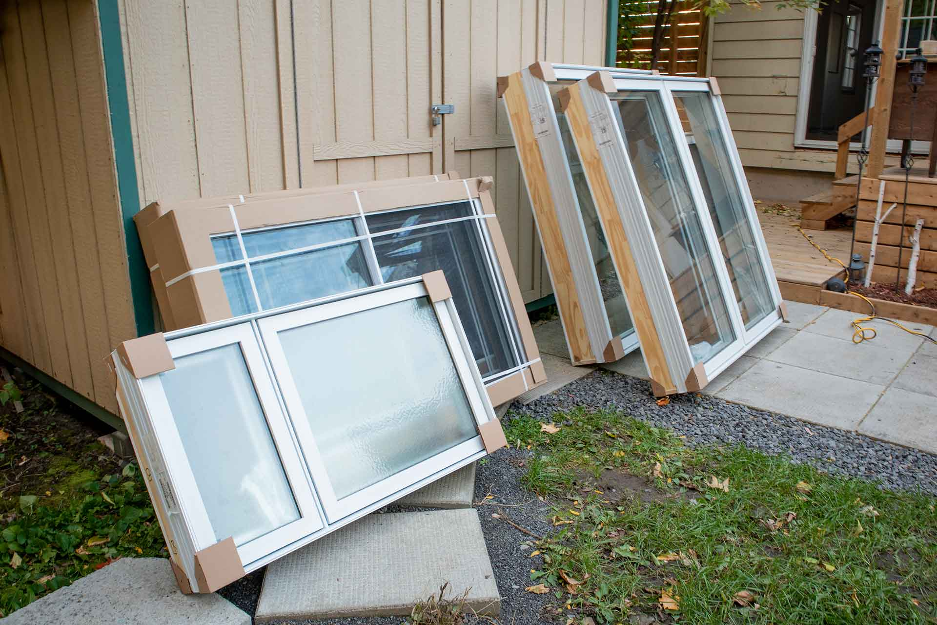 Replacement windows leaning up against a shed, awaiting installation.