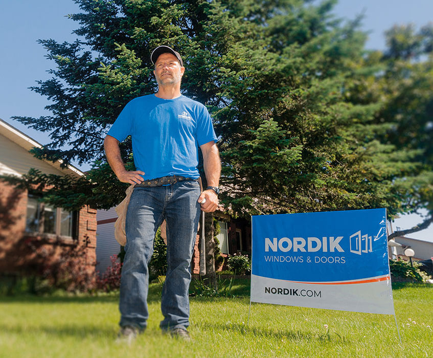A Nordik window installer poses on the lawn of a house with newly replaced windows.